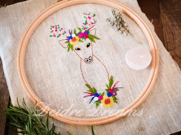 Photo of Crowned deer finished embroidery shown with loose hoop on top